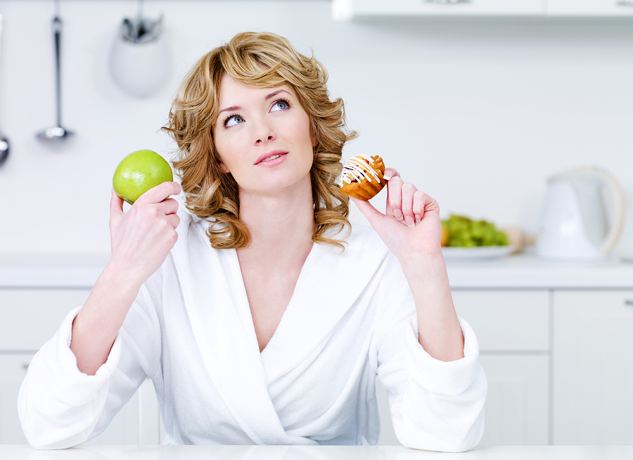 Woman choosing between healthy food and caloric food
