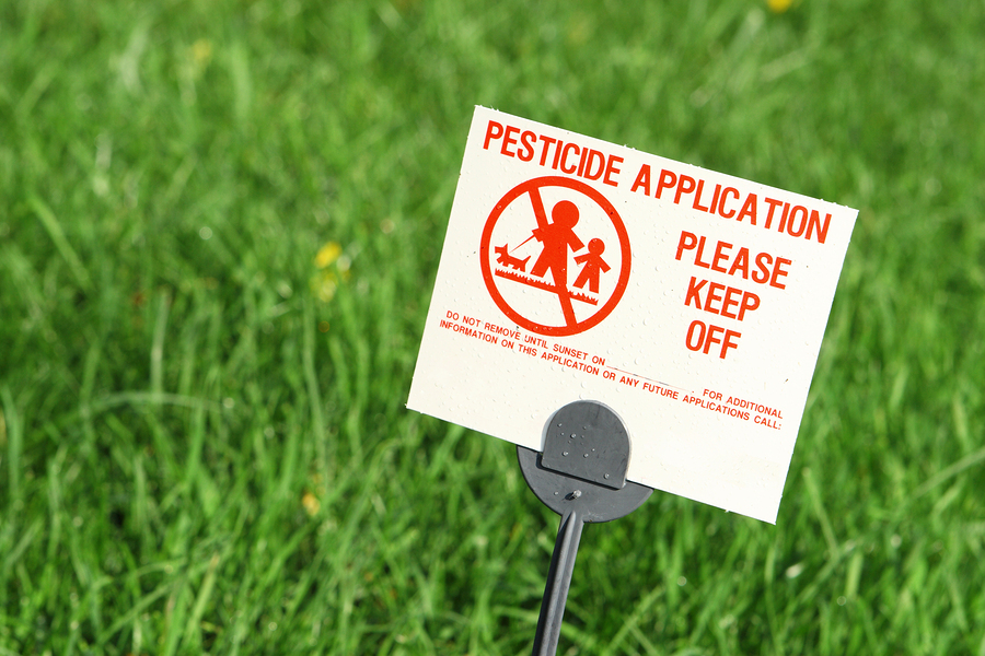 Pesticide warning sign on a bright green lawn